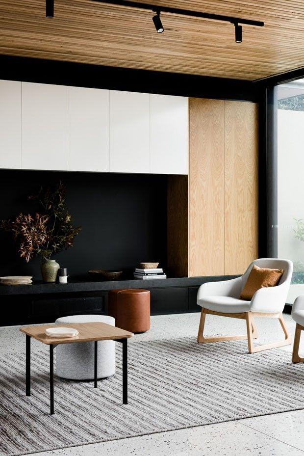 Một căn phòng đầy sự đối lập với ghế trắng, tường đen và đồ gỗ nhạt màu