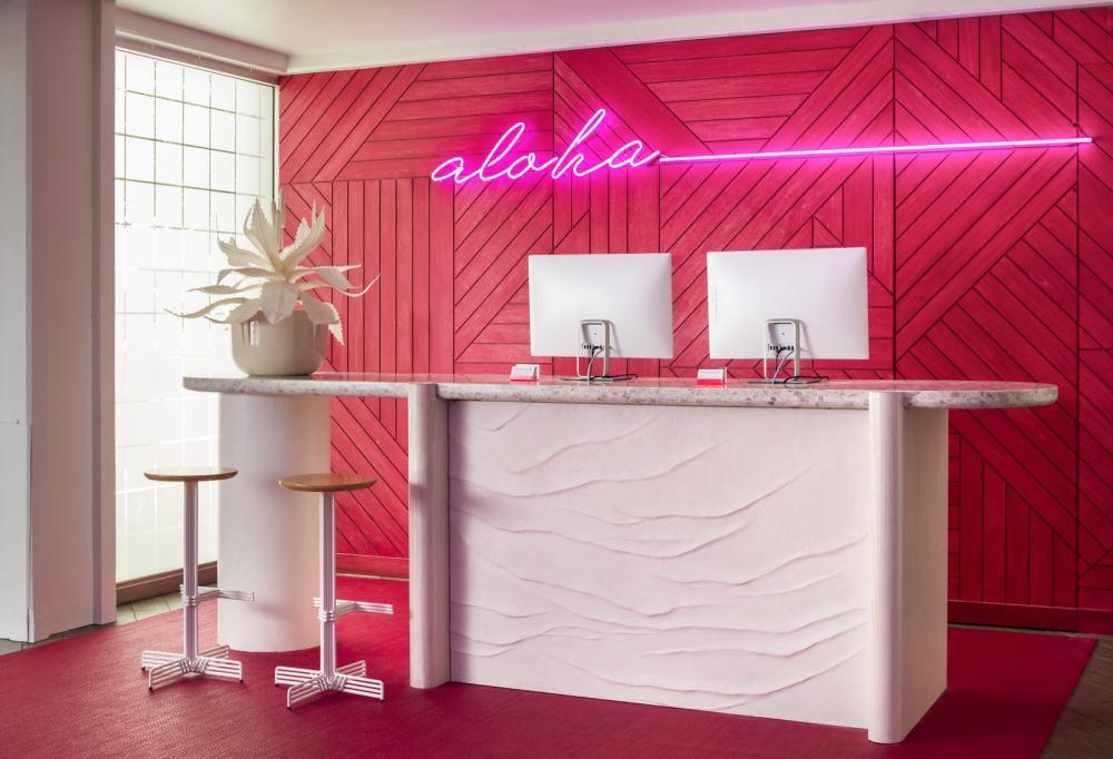 """Bức tường tại quầy lễ tân có màu hồng neon như làm nổi bật hơn logo """"Aloha"""" của khách sạn"""