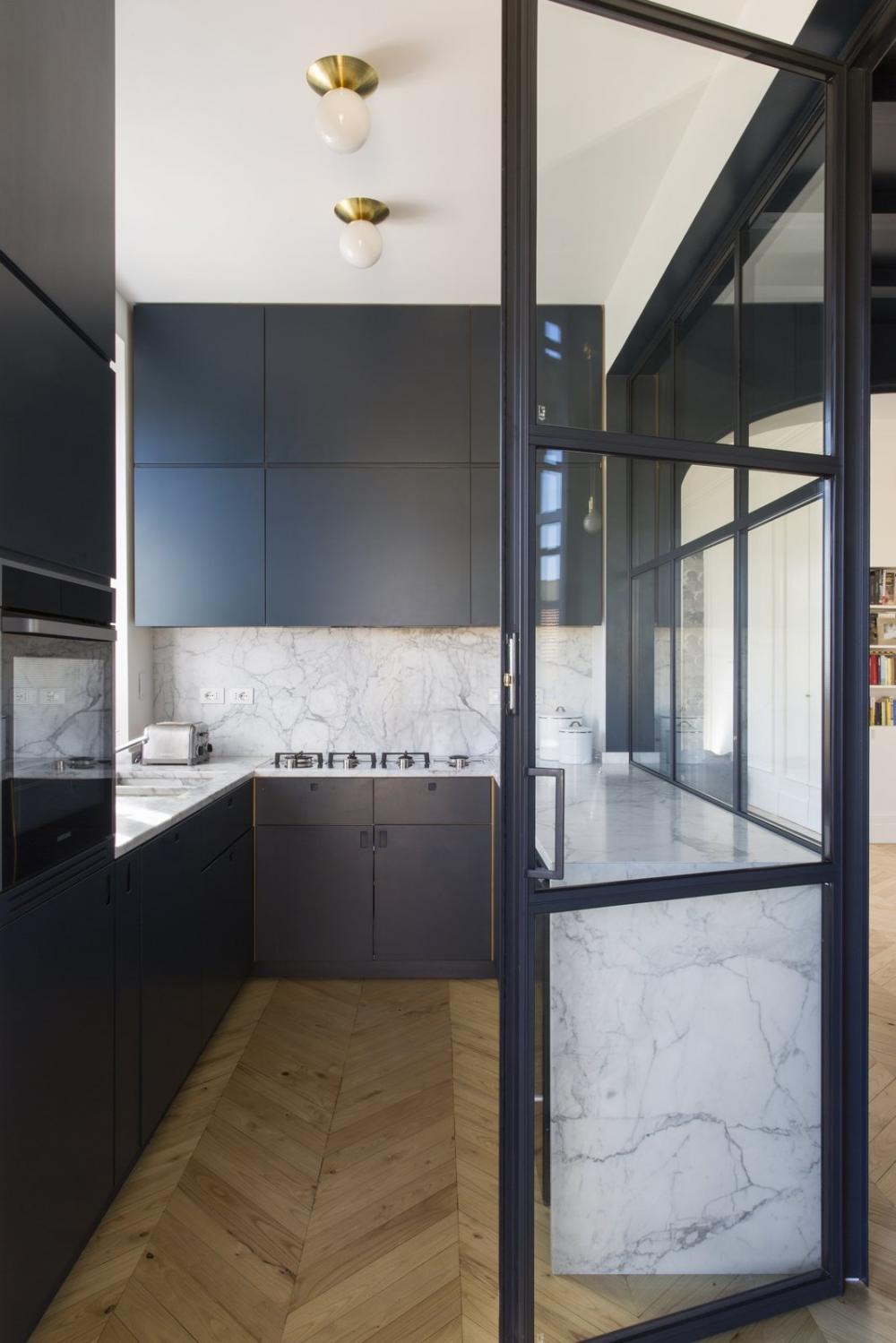 Cửa sổ bao quanh nhà bếp hiện đại và đẹp mắt. Đá cẩm thạch có vân sâu được sử dụng cho bề mặt bàn và backsplash.