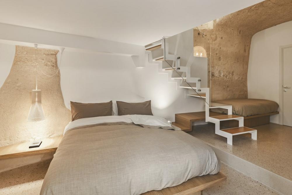 Phòng ngủ thiết kế với gam màu trung tính, tương đồng với màu của vách hang động