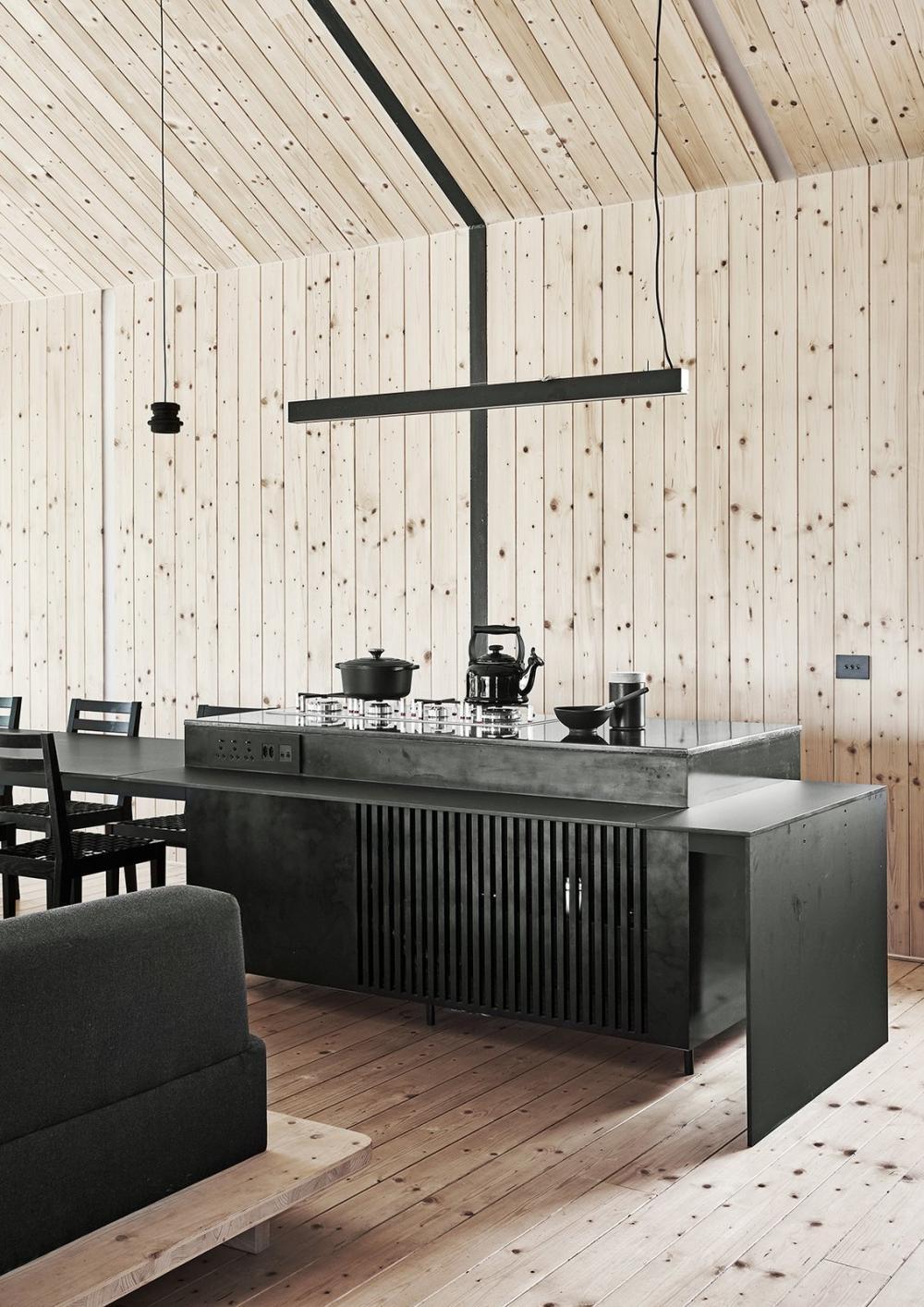 Bàn ăn là một phần mở rộng của quầy bếp, có bề mặt bằng đồng mạ đen. Đèn mặt dây chuyền khá nhỏ, giúp chiếu sáng cho khu vực nấu ăn