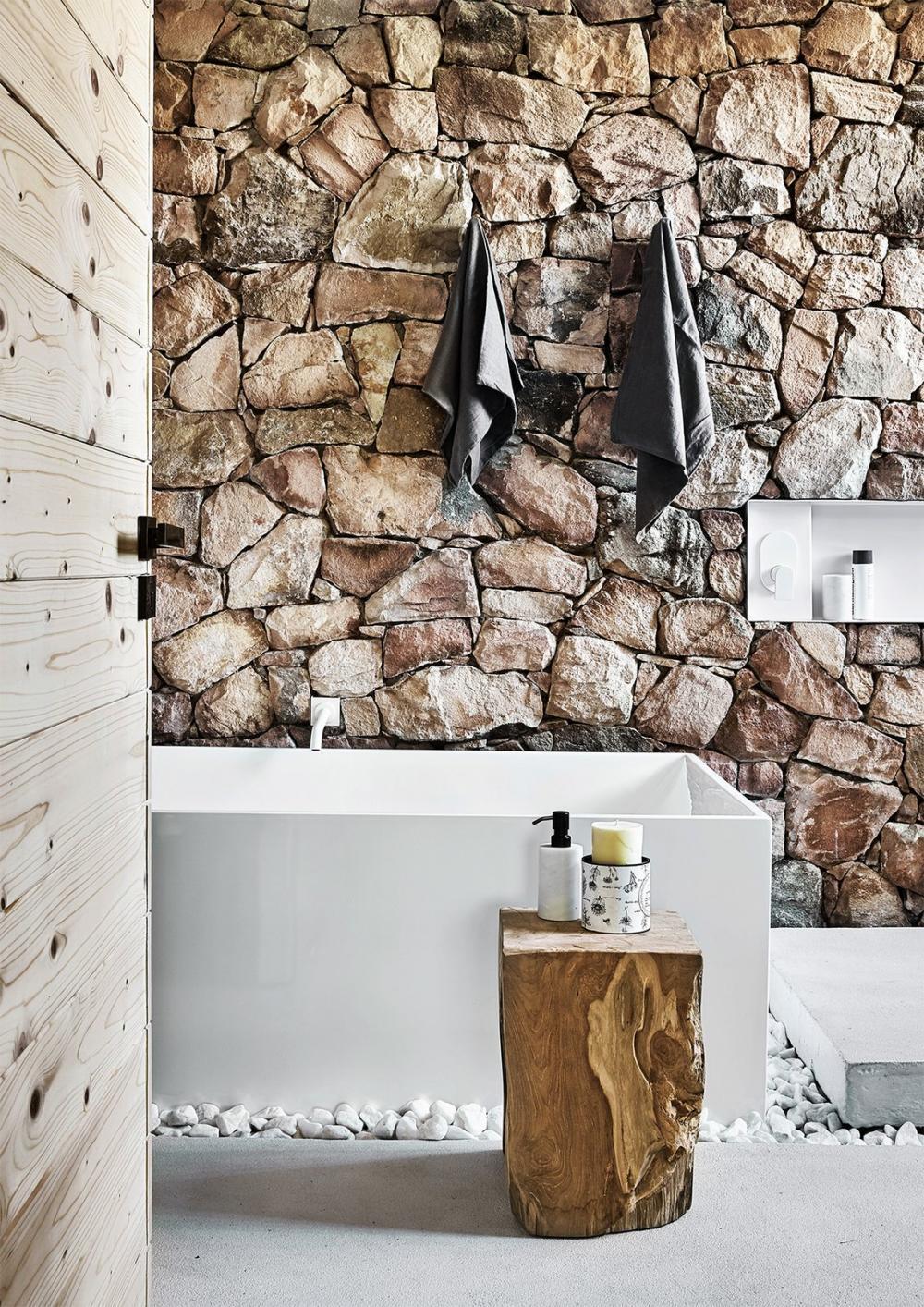 Điểm nhấn của phòng tắm chính là những bức tường làm bằng đá thô