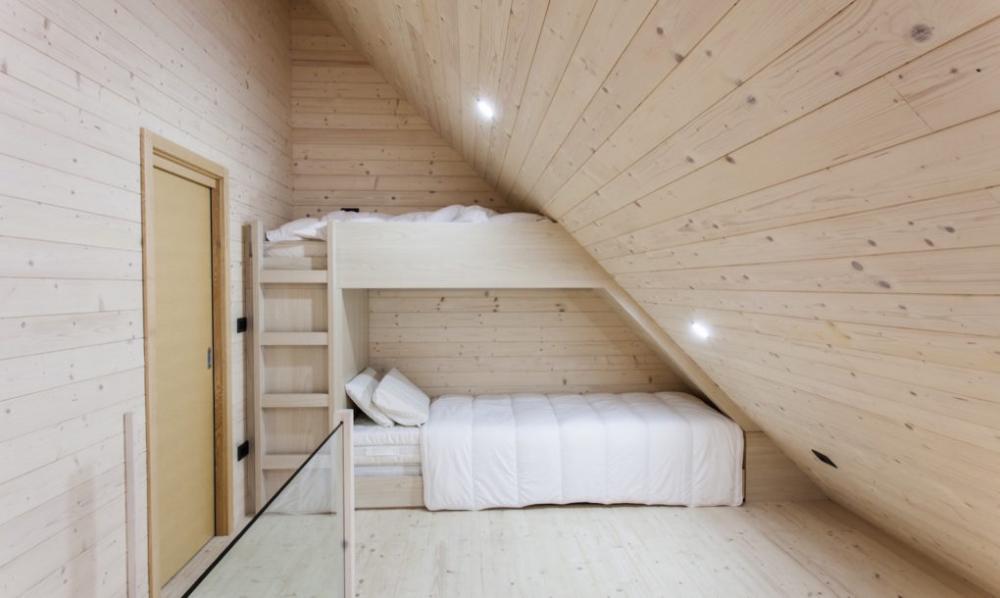 Giường ngủ được bố trí tại khu vực áp mái vừa mang lại góc riêng tư vừa tận dụng triệt để những góc cạnh của ngôi nhà