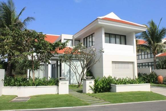 Bên ngoài một ngôi nhà kiểu biệt thự màu trắng mái đỏ, phía trước có sân vườn, xung quanh nhiều cây cối.