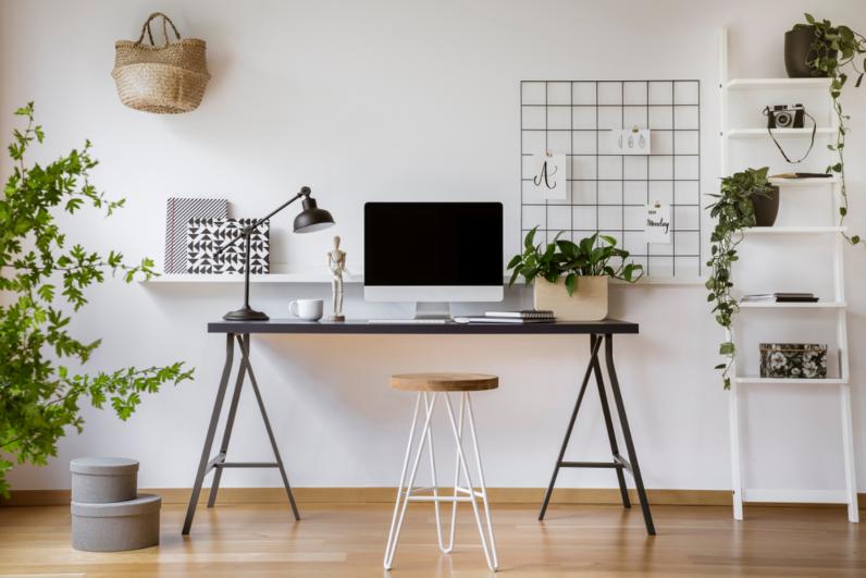 Phòng làm việc tại nhà gồm bàn đơn giản, laptop, đèn, các chậu cây xanh