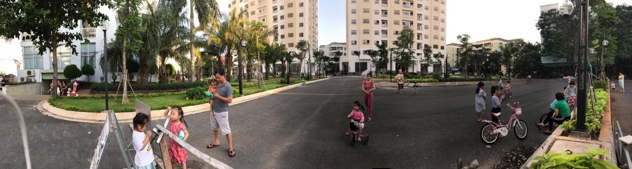 Nhiều người lớn và trẻ em đang chơi đùa tại sân một dự án chung cư