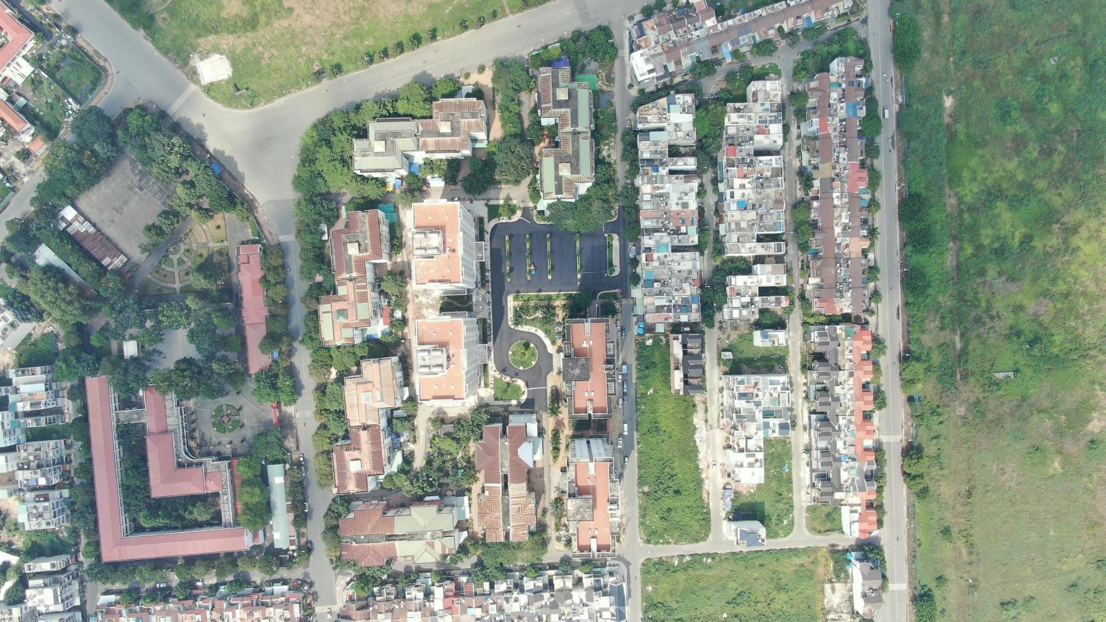 Ảnh chụp một góc thành phố từ trên cao với nhiều tòa nhà, cây xanh và con đường