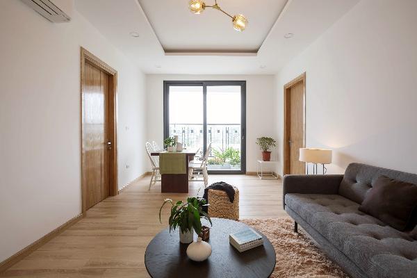 hình ảnh phòng khách tiện nghi với chiếc bàn gỗ tròn, sofa nỉ màu ghi đậm