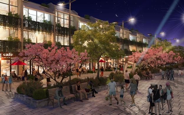 Nhiều người đang ngồi chơi và đi lại trên con đường ngập tràn hoa và cây xanh, phía sau là một khu shophouse