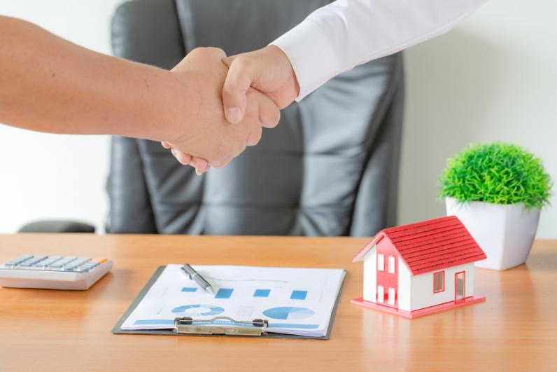 Hình ảnh bắt tay nhau mua nhà, gần bàn làm việc, trên có mô hình ngôi nhà, chậu cây