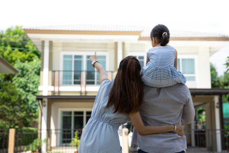 Một gia đình ba người bố, mẹ, con đứng trước ngôi nhà