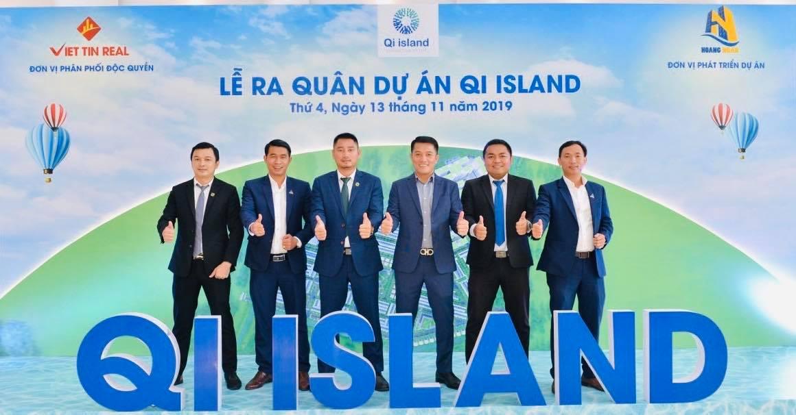 ^ người đàn ông mặc vest giơ tay ra phía trước và chữ Qi Island màu xanh