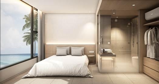 Một phòng ngủ ven biển với ga giường màu trắng, nhà vệ sinh kính trong suốt