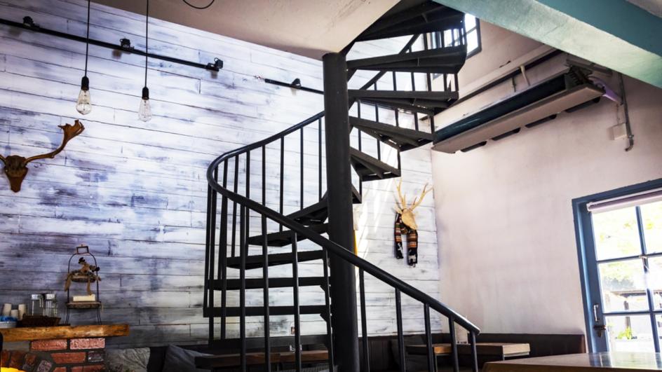 Cầu thang xoắn màu đen ở giữa, xung quanh là tường ốp gỗ, điều hòa, đồ trang trí.