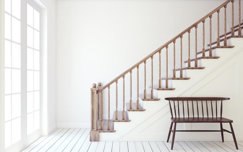Ảnh chụp cầu thang lan can gỗ hướng ra cửa, ghế ngồi, tường và sàn nhà màu trắng