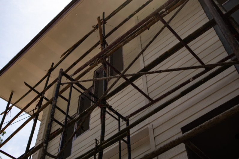 Ảnh chụp từ dưới lên một phần nhà và mái, giàn giáo thi công.