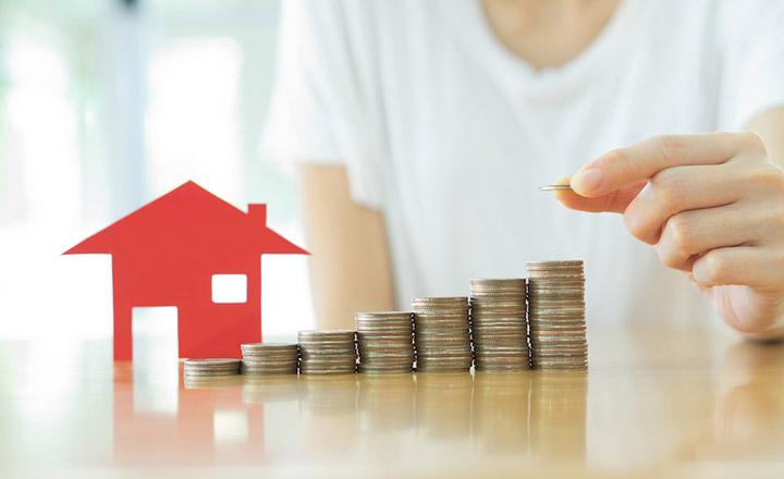 Một bàn tay đang xếp các đồng xu thành 7 cột bên cạnh mô hình ngôi nhà