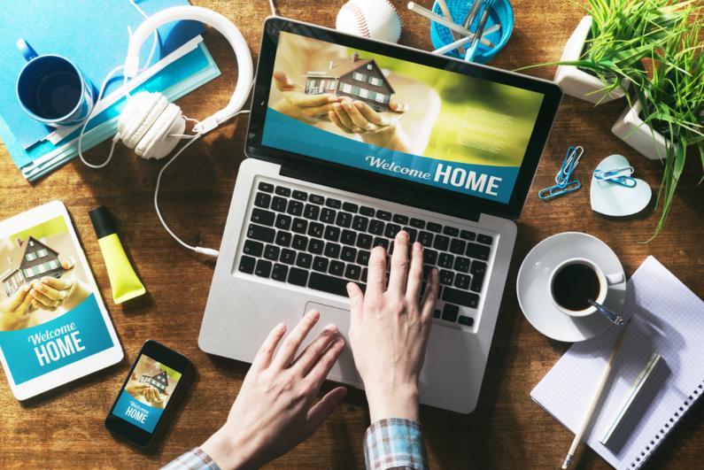 Bàn tay gõ bàn phím trên laptop đặt trên bàn, xung quanh là cốc cafe, sổ, sách, tai nghe...