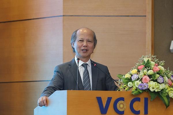 Người đàn ông lớn tuổi, đầu hói, mặc vest đứng trên bục sân khấu, cạnh giỏ hoa lớn.