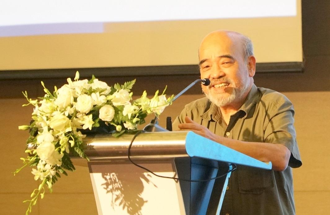 Chân dung người đàn ông có râu, mặc áo sơ mi ngắn tay, đứng trên bục phát biểu, cạnh lẵng hoa màu trắng.