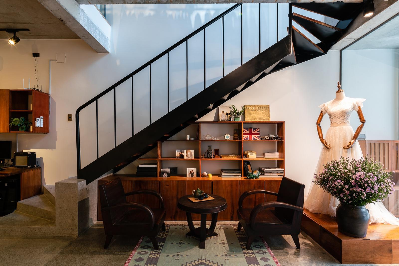 Cầu thang màu đen, bên dưới là phòng khách với kệ đồ, bàn ghế gỗ, manocanh mặc váy trắng, lọ hoa...