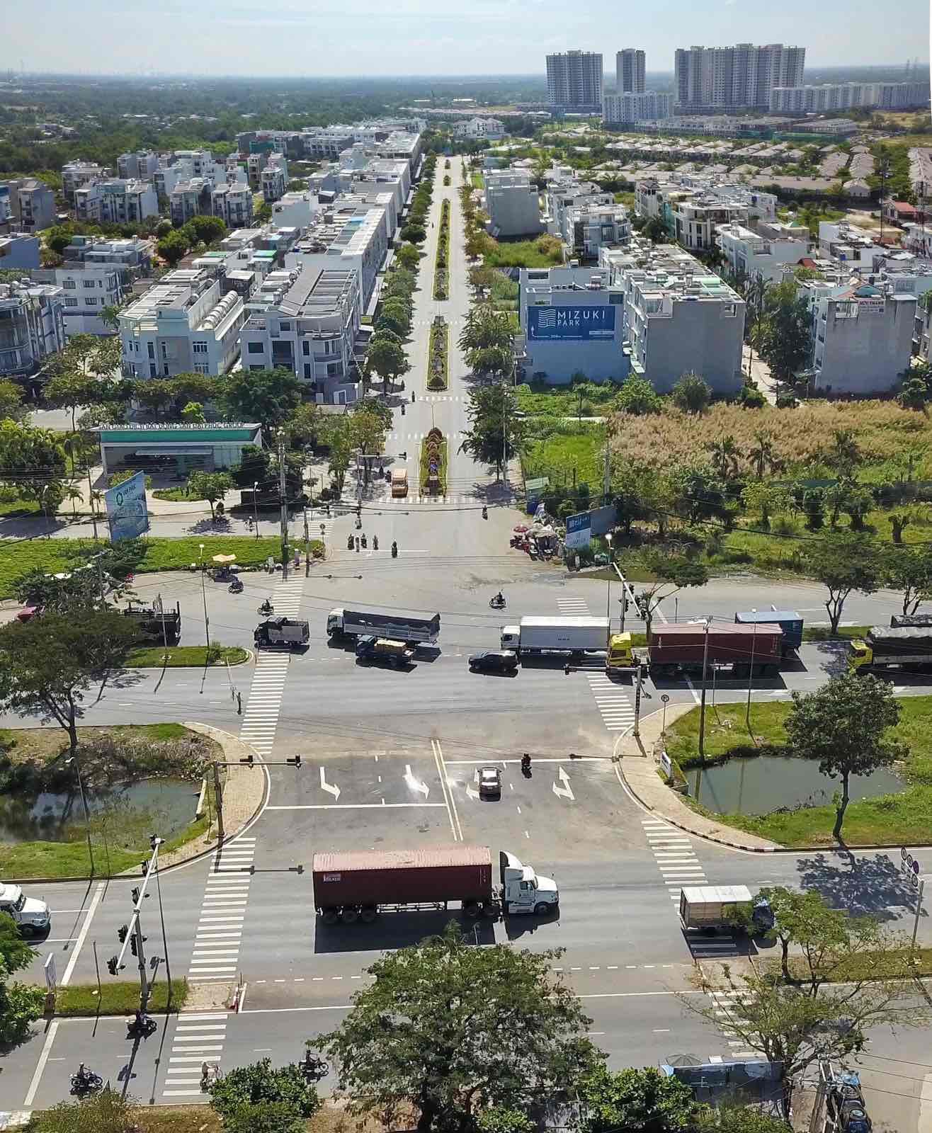 Hình ảnh 1 con đường có đông phương tiện đang di chuyển, hai bên đường là các công trình nhà ở xen lẫn cây xanh