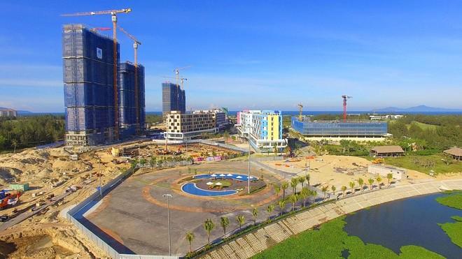 Dự án căn hộ khách sạn condotel Cocobay với nhiều tòa nhà cao tầng đang xây dựng nằm gần sông, phía trước là bãi đất trống
