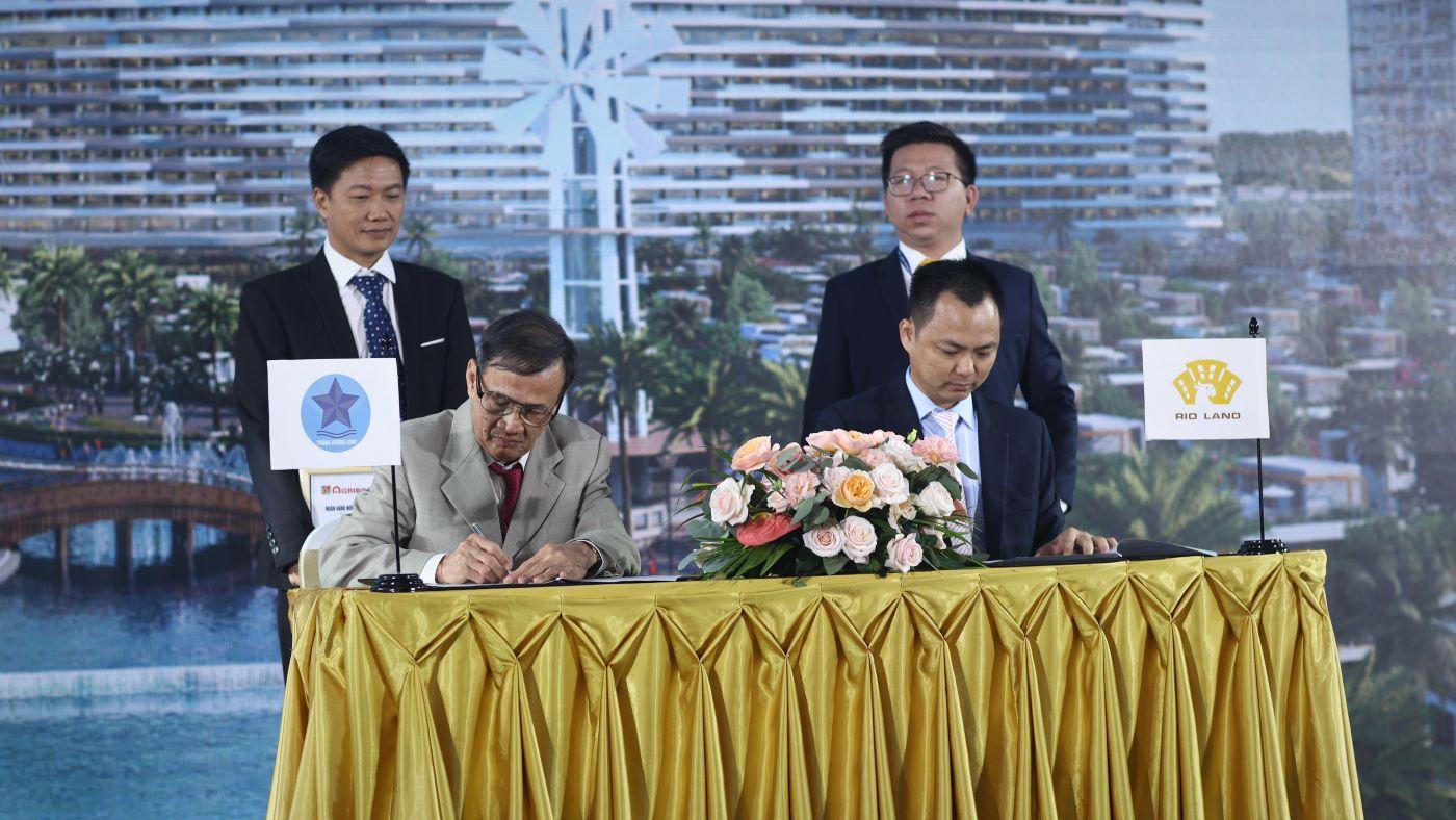 Trong ảnh có 4 người đàn ông mặc vest, hai người ngồi ký, hai người đứng phía sau