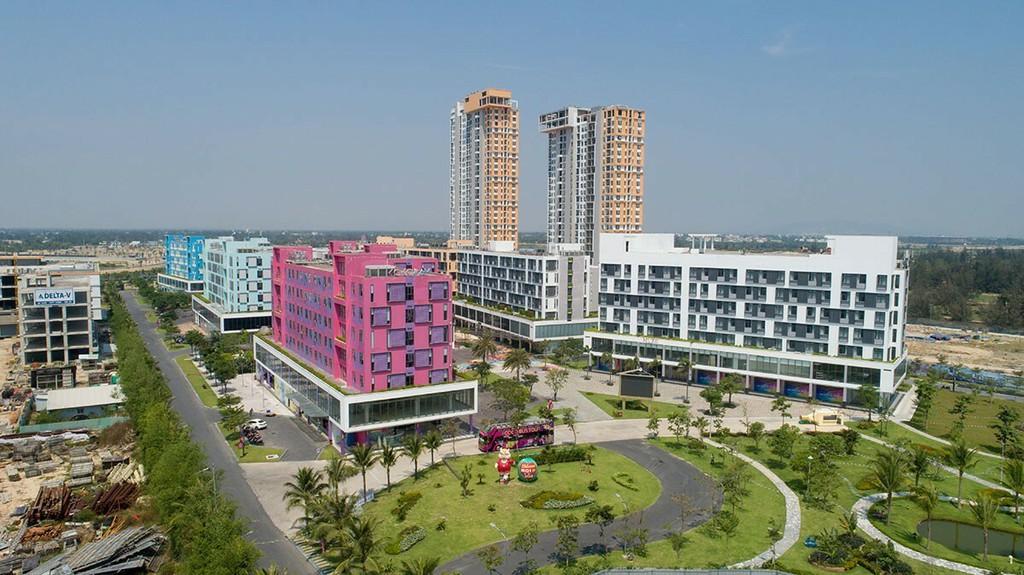 Dự án condotel Cocobay Đà Nẵng gồm nhiều tòa nhà cao tầng đã xây dựng, bên cạnh có công viên cây xanh và đường đi