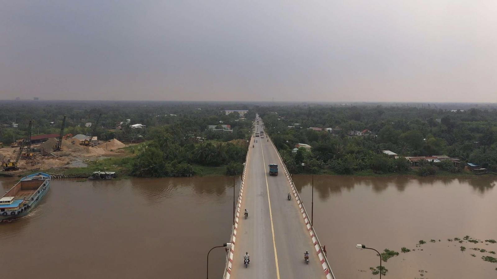 Hình ảnh một cây cầu bắc qua sông, phía bên kia sông là khu dân cư với nhiều cây xanh