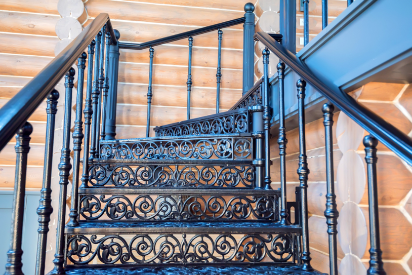 Ảnh chụp cận cảnh một cầu thang bằng kim loại màu đen, bậc thang hoa văn.