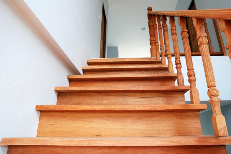 Ảnh chụp cận cảnh một cầu thang bằng gỗ màu nâu vàng.