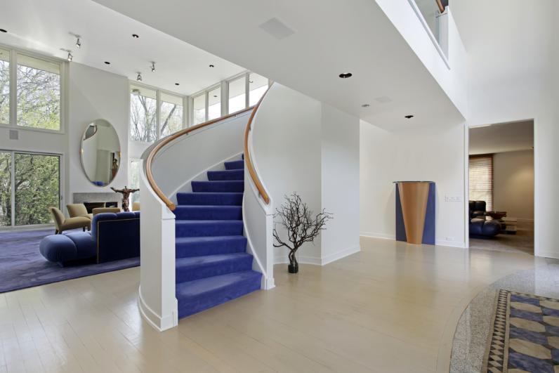 Tầng trệt ngôi nhà với các bức tường trắng, chính giữa là cầu thang có các bậc thang màu tím.
