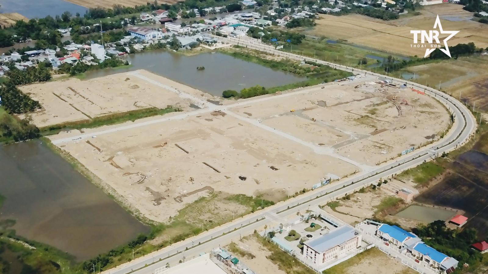 Công trường dự án với bãi đất trống cạnh sông và nhiều nhà ở hiện hữu