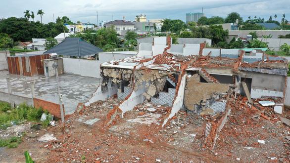 nhà ở xây dựng sai phép đã bị tháo dỡ, xung quanh có nhiều cây cối, nhà ở khác
