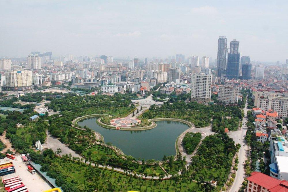 một góc TP. Hà Nội nhìn từ trên cao với công viên cây xanh và hồ nước trung tâm, xung quanh có nhiều công trình nhà ở, đường đi lại