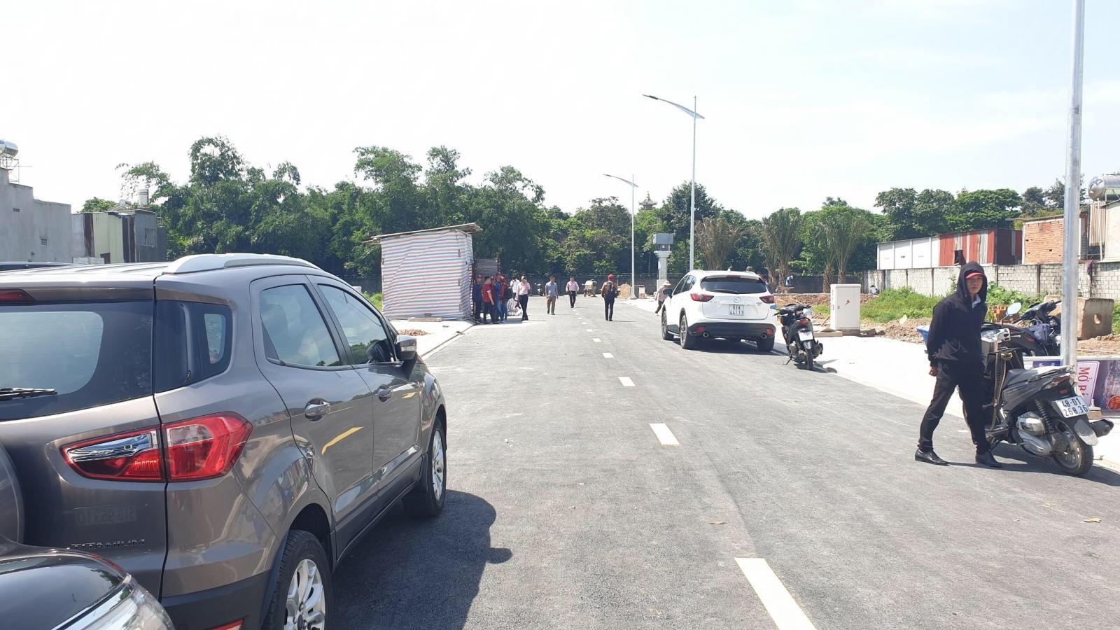 Ô tô, xe máy, một số người đi lại trên con đường lớn dẫn vào dự án bất động sản, phía trong nhiều cây cối.