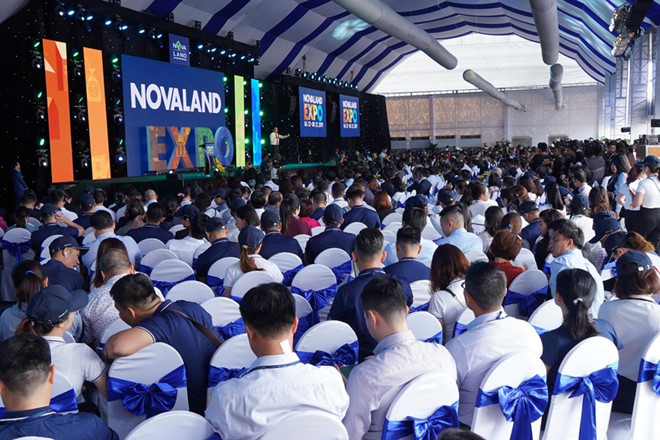 Hội trường triển lãm có mái che với rất đông người đang ngồi hướng lắng nghe người trình bày trên sân khấu