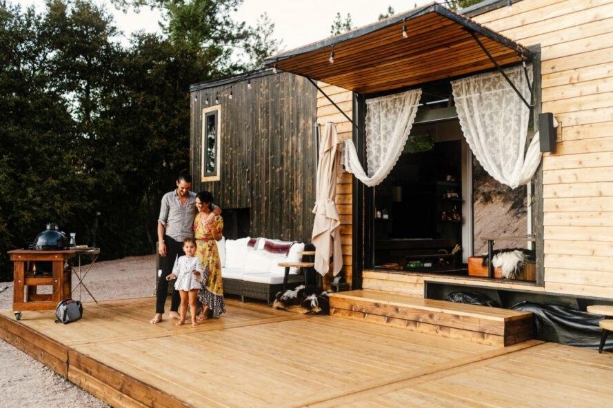 gia đình 3 người đang đứng trước sàn gỗ ngoài trời
