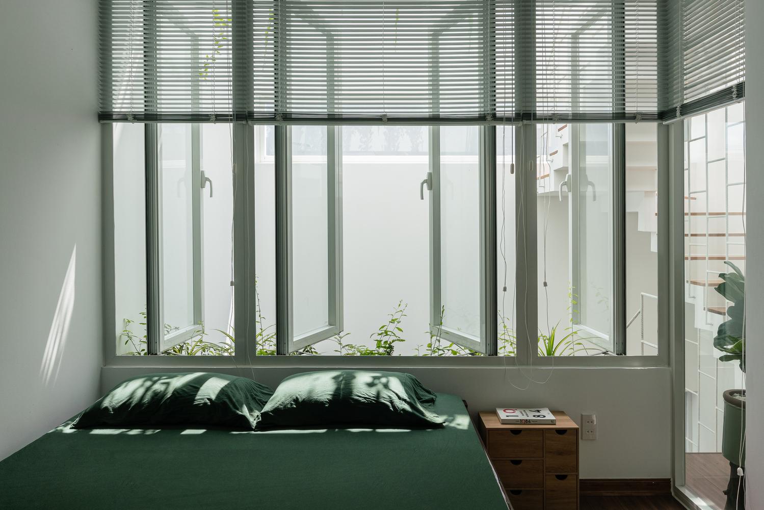 giường ngủ cạnh cửa sổ