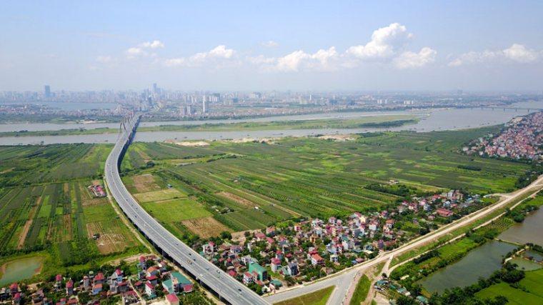 Khu đất trống ven sông có đường lớn và cầu chạy qua nối với khu nhà ở phía xa