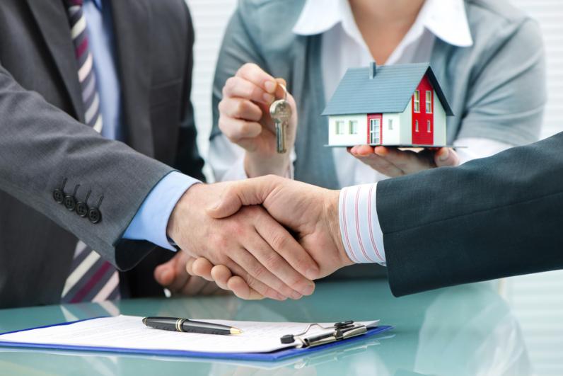 Hình ảnh hai người đang bắt tay và một người đứng bên cạnh cầm chìa khóa và mô hình ngôi nhà