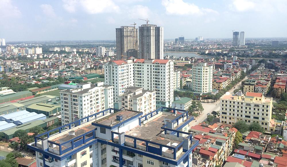Một góc thành phố có con đường chạy qua, nhiều tòa nhà cao tầng và thấp tầng nằm sát nhau, phía xa có hồ nước