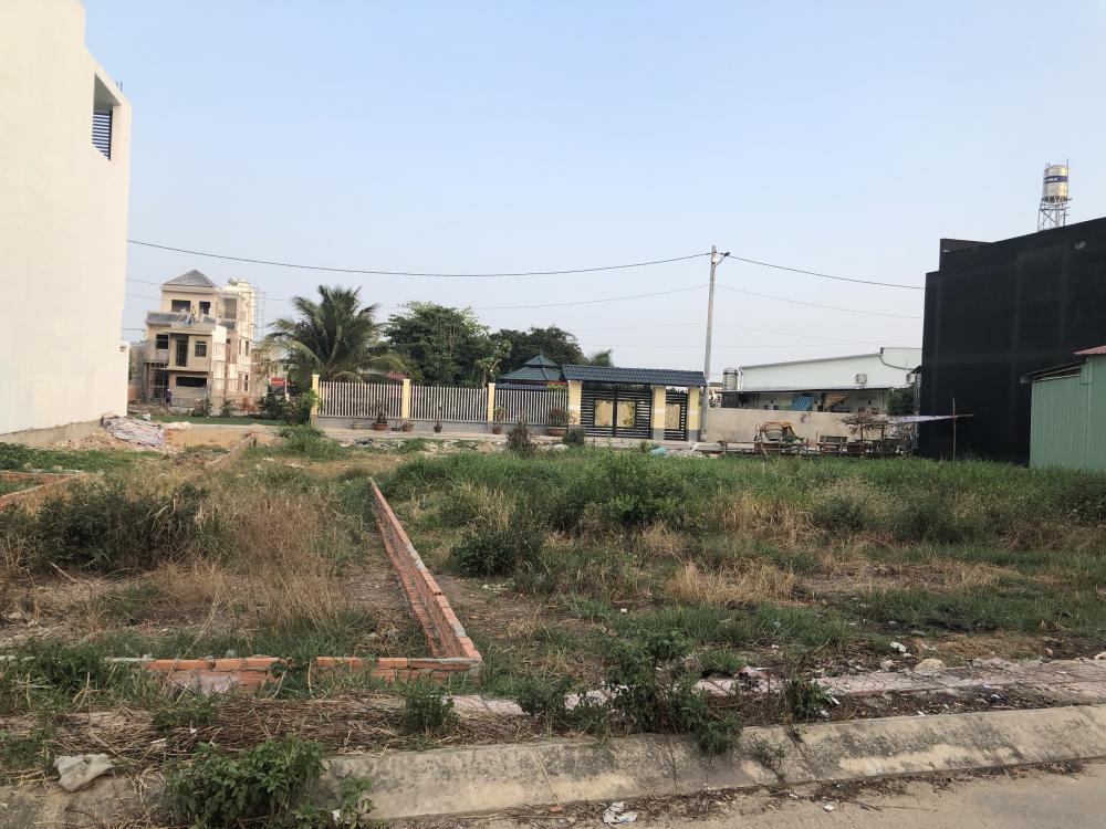 Ảnh chụp một bãi đất trống, bên cạnh là một số công trình nhà ở