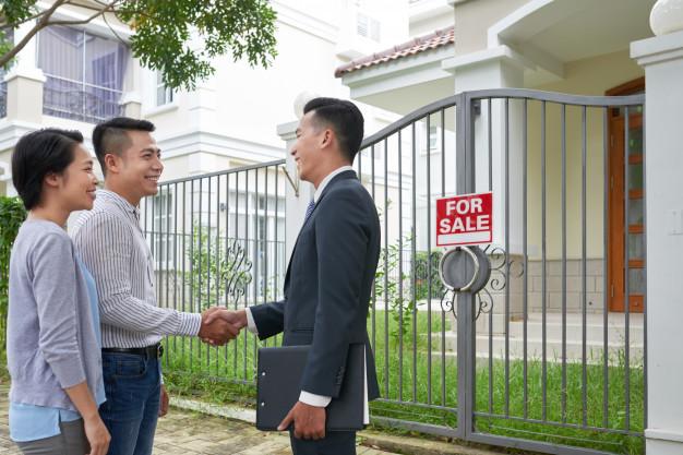Hai người đàn ông đang bắt tay và một người phụ nữ đứng trước ngôi nhà treo biển bán, có cây xanh và cửa sắt