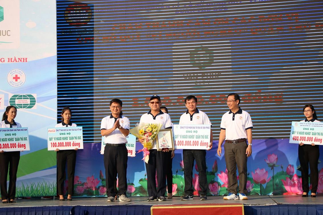 Nhiều người mặc áo phông trắng đứng nhận giải thưởng trên sân khấu