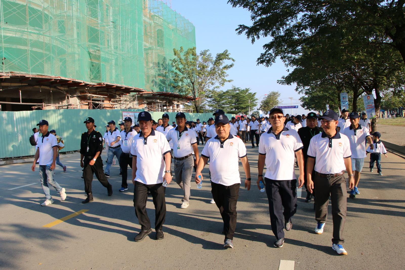Nhiều người mặc áo phông trắng đang đi bộ tại một con đường trong khu đô thị