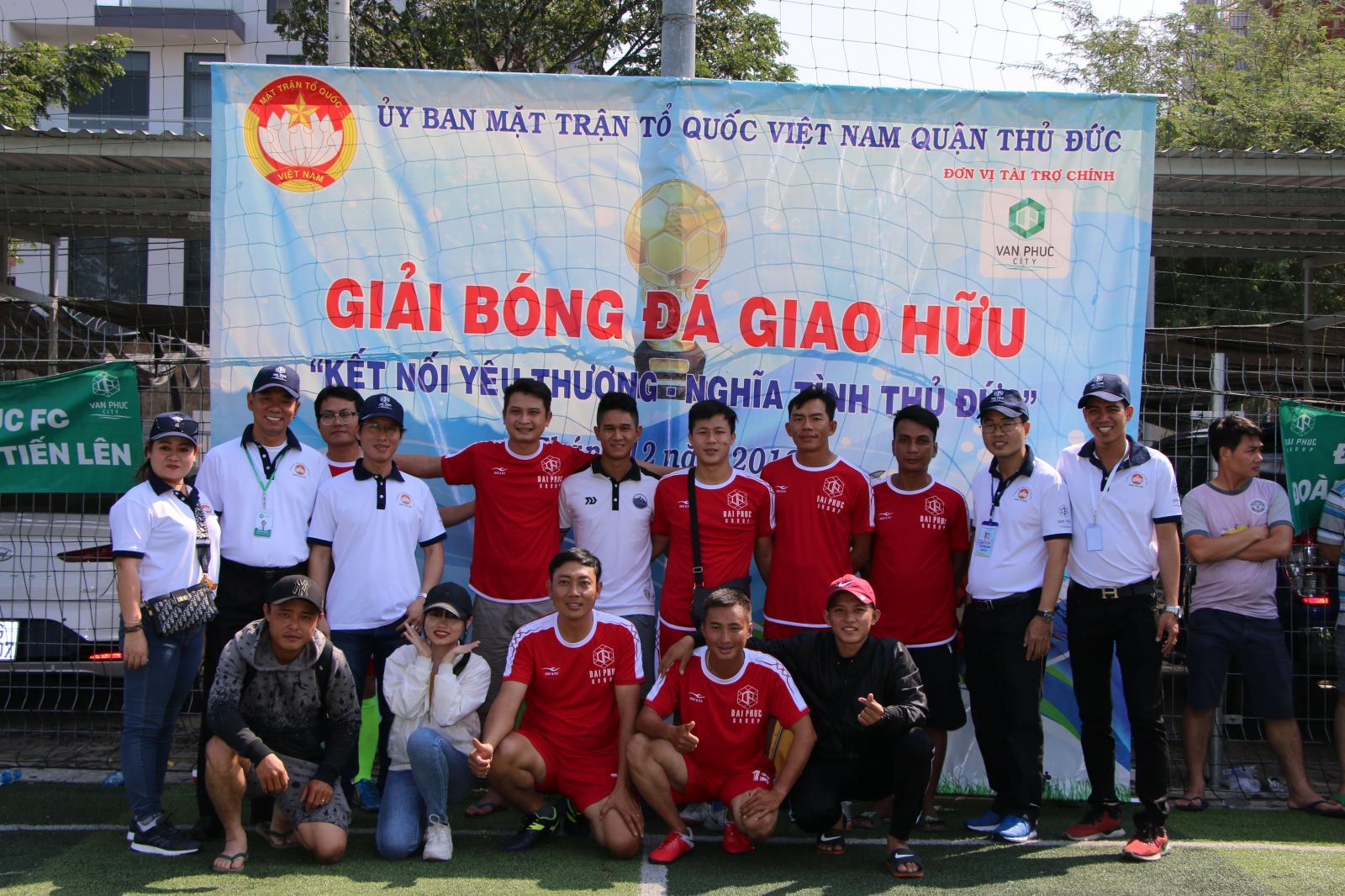 1 đội hình người phía trước ngồi, phía sau đứng trước 1 tấm phông giải bóng đá