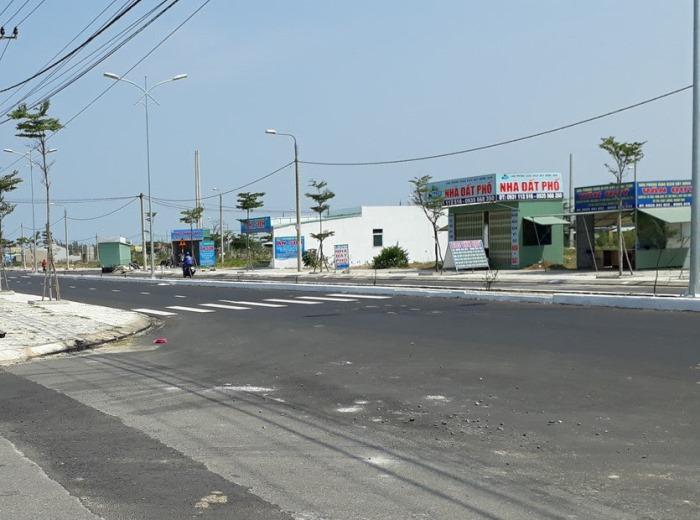 Bên trong một dự án đất nền có các ki ốt nhỏ nằm dọc bên đường lớn, vỉa hè có các cây xanh mới trồng.