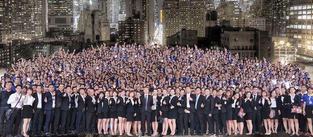 Ảnh chụp một tập thể rất nhiều người mặc vest đen phía trước và áo màu xanh phía sau.
